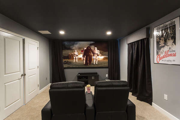 The second floor features a movie theater room with a projection screen and comfortable seating