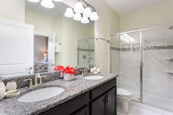 The ensuite master bathroom has granite counters and a walk in shower