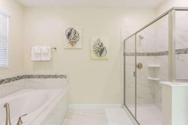 The bathroom has a glass shower and large bathtub