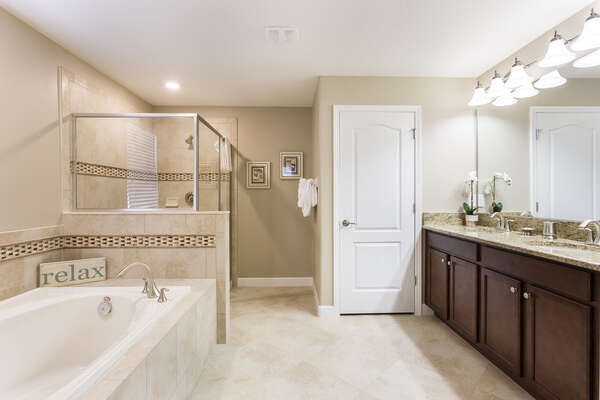 The ensuite bathroom has ample space with a glass shower and soaking tub