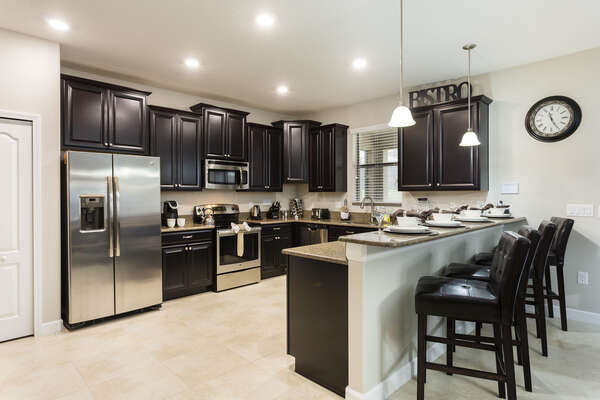 The fully-equipped kitchen has stainless steel appliances, granite counters and breakfast bar seating for 4
