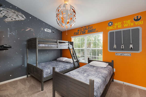 The kids bedroom features twin single bed, twin over full bunk bed, and a cool galaxy theme