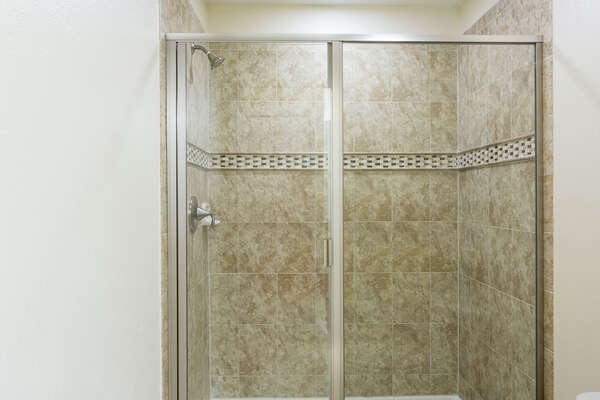 The ensuite bathroom features a walk in shower
