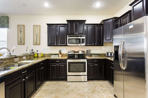 The fully-equipped kitchen features stainless steel appliances and granite countertop