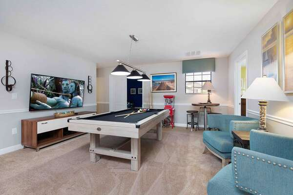This lounge area features an a pool table, bar seating, and a 50-inch SMART TV
