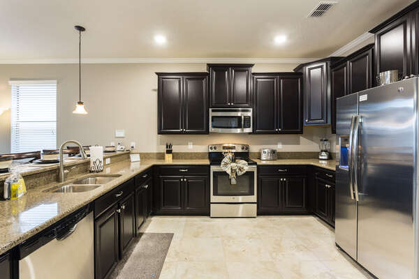 The fully equipped kitchen features stainless steel appliances and granite countertops