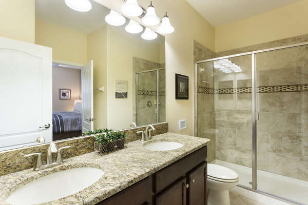 An upstairs family bathroom with dual sinks and a glass walk in shower