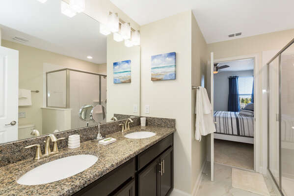 A Jack-n-Jill bathroom for the master bedroom features dual vanity and walk-in shower