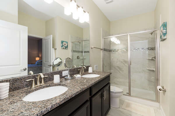 A full shared bathroom with dual vanity and walk-in shower