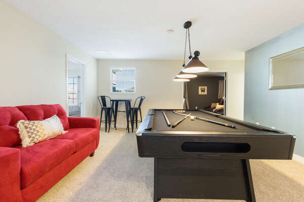The second-floor loft area features comfortable seating and pool table