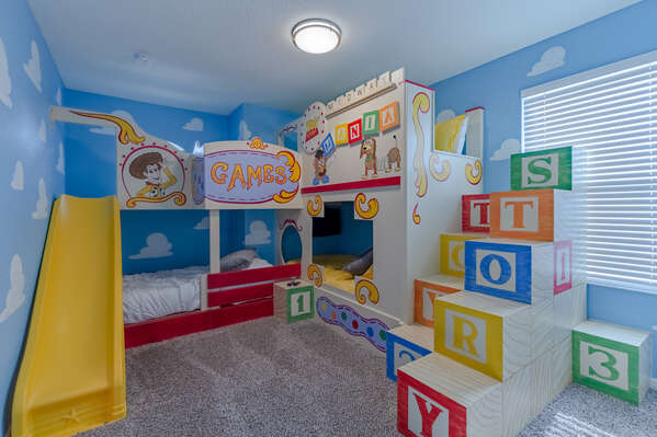 Kids will feel like toys in this fun custom bedroom that even includes a slide!