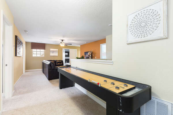 The upstairs loft area features shuffleboard