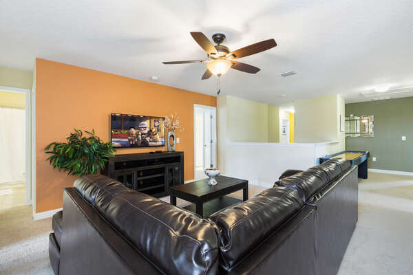 The loft area features a plush leather couch and TV for watching favorite shows together