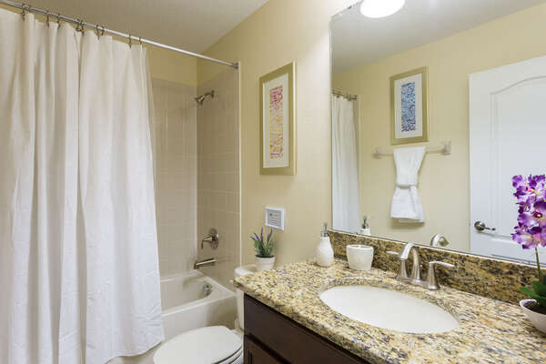 This upstairs family bathroom has a combination shower and tub with granite counters