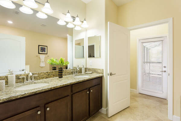 The ensuite master bathroom features access to the pool deck and plenty of space to get ready
