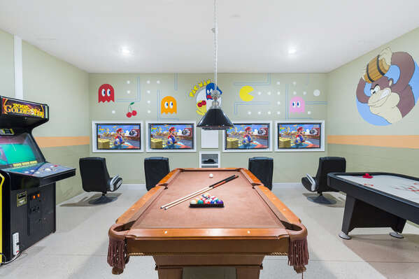 This fun arcade game room features a pool table, foosball table, air hockey table, multi-arcade games and a video game setup