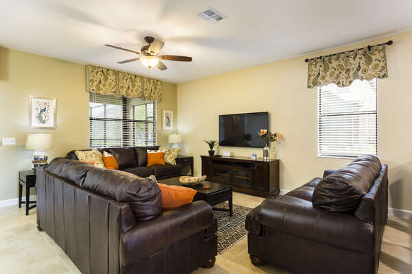 Spacious seating on the leather couches around the large flatscreen TV are great for the whole family to be together