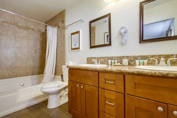 Dual Sink Vanity, Toilet, and Shower-Tub Combination.
