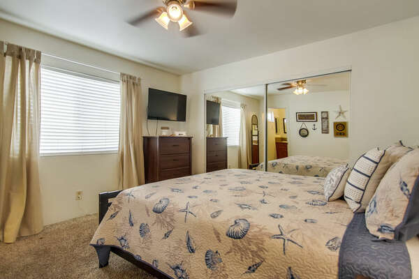 Bedroom with Large Bed, Dresser, TV, Ceiling Fan, and Mirror Closet Doors.