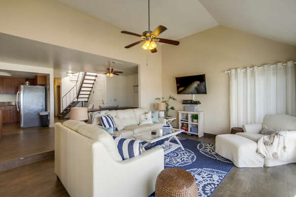 Open Area with Sofas, TV, Ceiling Fans, Staircase, and the Kitchen Refrigerator.