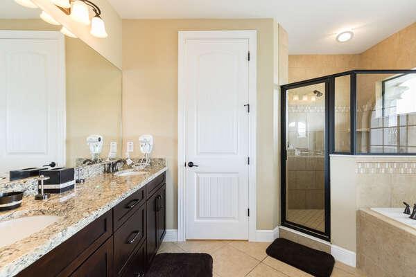 The en-suite bathroom has a dual vanity, walk-in shower, and garden tub