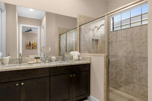 The ensuite bathroom has a glass walk-in shower and granite his and hers sink
