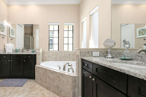 The ensuite bathroom has a large soaking tub and granite counters