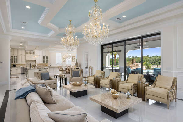 The open living space boasts crystal chandeliers and granite end tables