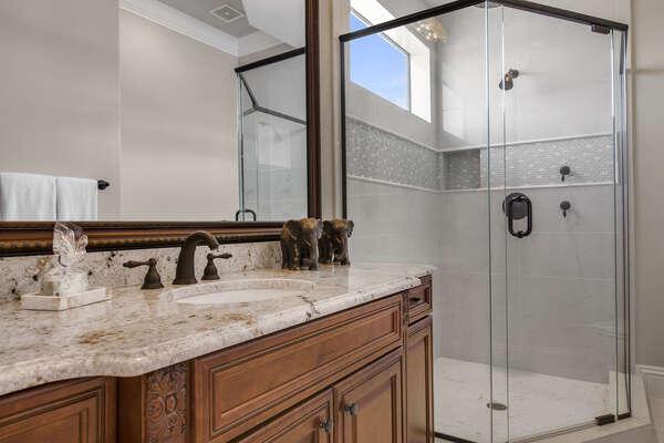 The en-suite bathroom offers a rainfall shower head