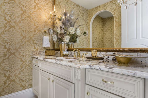 This powder room has nothing but the best with granite counter tops and gold fixtures