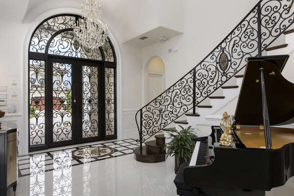 Be wowed by the foyer with a sweeping staircase and grand piano with an 8,000 song library