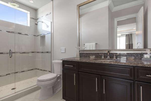 The en-suite bathroom features a glass walk-in shower
