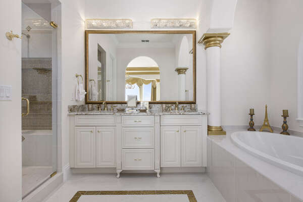 The en-suite bathroom is elegantly appointed and features both a soaking tub and glass shower