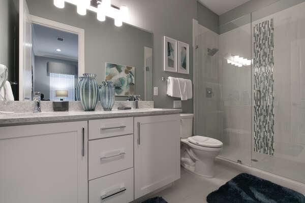 The master en-suite bathroom features a glass door walk in shower