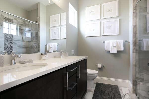 The en-suite bathroom has a glass door walk-in shower and dual vanity