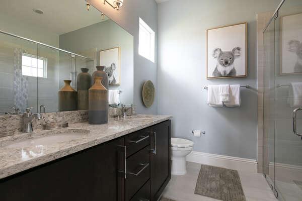 Master en-suite bathroom features glass door walk-in shower and dual vanity