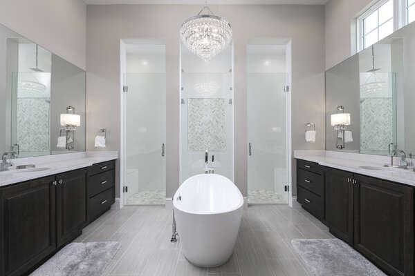 En-suite bathroom features glass door walk-in shower with large tub, and dual vanity