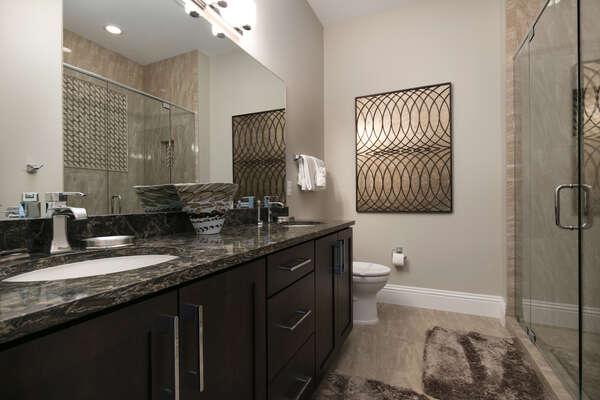 The en-suite bathroom with glass door walk-in shower and dual vanity