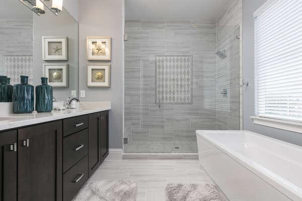 The en-suite bathroom features glass door walk-in shower and garden tub