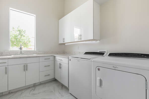 The main floor laundry room with a full sized washer and dryer