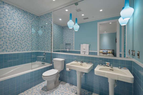 The en-suite bathroom has a 6-foot soaking tub and pedestal sinks