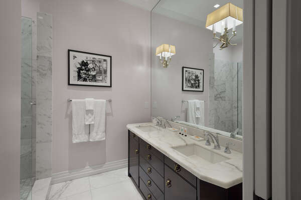 The en-suite bathroom features vintage Hollywood Regency dual vanity and glass walk-in shower