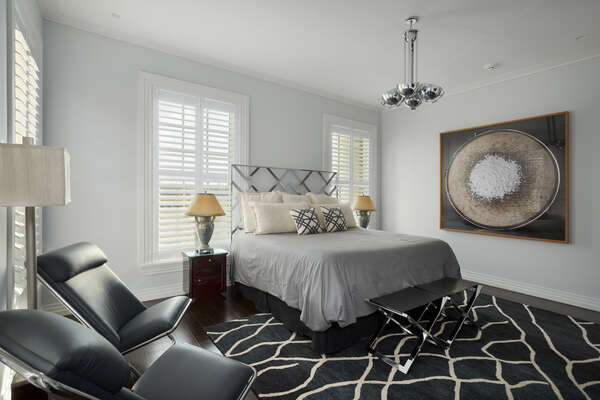 This bedroom features a sleek geometric king bed and 48-inch SMART 4K TV