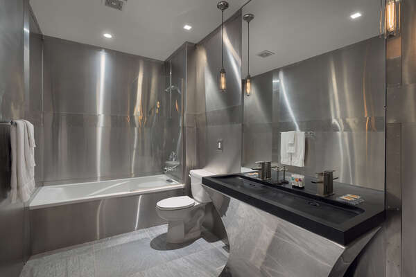 The en-suite bathroom features gleaming stainless steel walls and black granite vanity