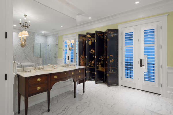 Master en-suite bathroom has a dual antique Federal-style vanity and Coromandel screen