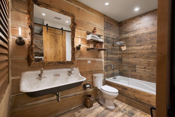 The en-suite bathroom has a 6-foot tub, brockway sink, and custom built Rocky Mountain timber mirror