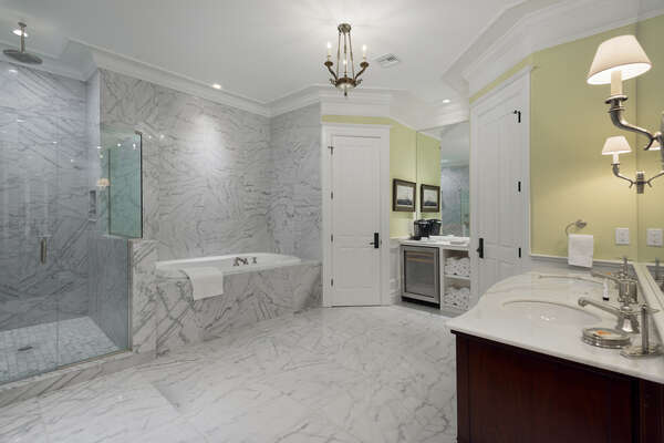 The en-suite bathroom has a luxurious garden tub, glass door walk-in marble shower, and morning bar