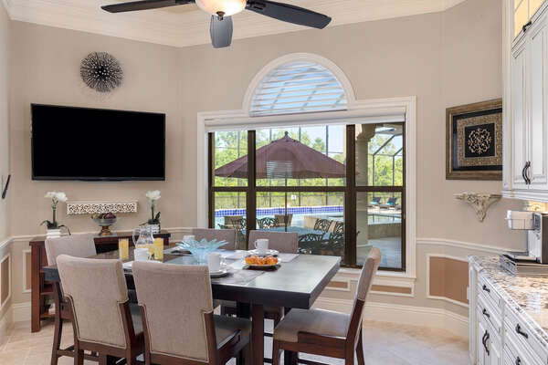 Breakfast nook seating with a TV and pool views