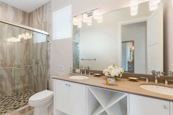 En-suite bathroom with glass walk-in shower and dual vanity