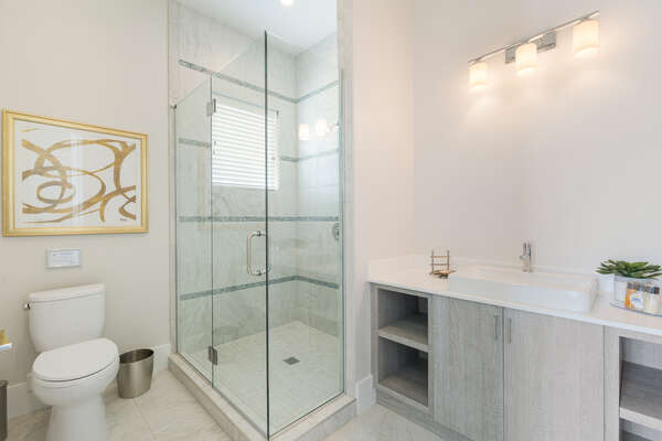 The en-suite bathroom features a glass door walk-in shower